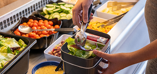 The eco-friendly lunchbox being filled up with salad