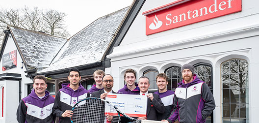 photo of some of the Tennis Foundation student volunteer coaches standing outside the University Santander branch with some of the bank staff holding a cheque