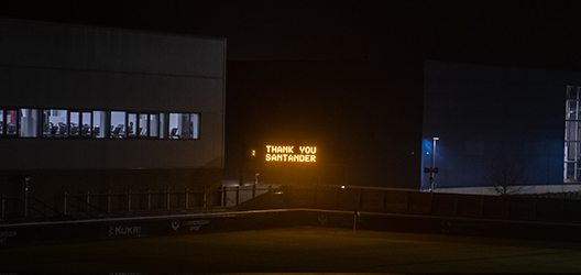 photo of rugby pitch in the evening with 'Thank you Santander' written on the rugby pitch screen