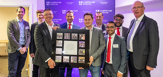 photo of University staff and Santander guests at the event holding a plaque that celebrated the 10-year partnership