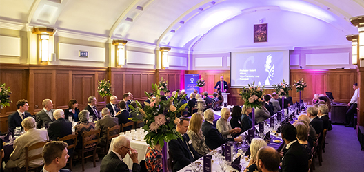 photo of Schofield Society dinner in the Council Chamber, with two long tables with members and VC Bob presenting at the head of the tables