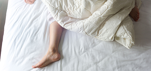 photo of a woman's feet hanging out of a duvet on a bed