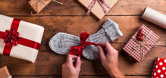 Pictured is someone wrapping socks for Christmas.