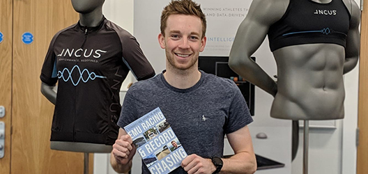 photo of student Tom Davies holding his new book 'Emu Racing and Record Chasing'