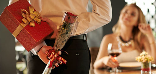 photo of man holding roses and a box of chocolates for his partner