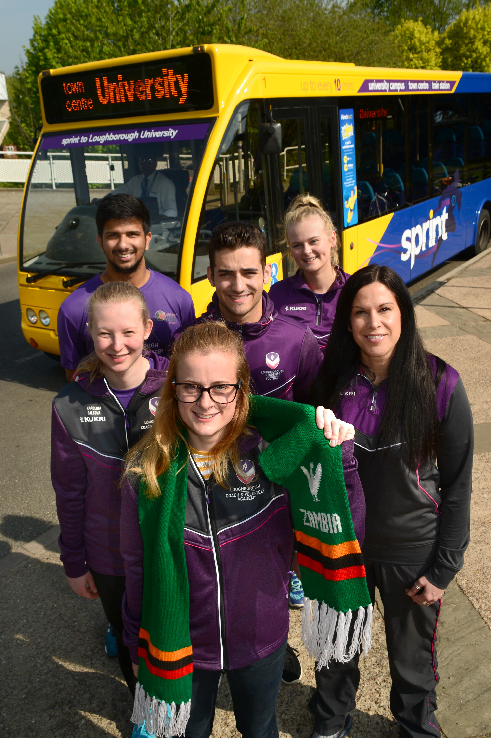 Photo of six students taking part in Zambia volunteering project, with sprint bus behind them
