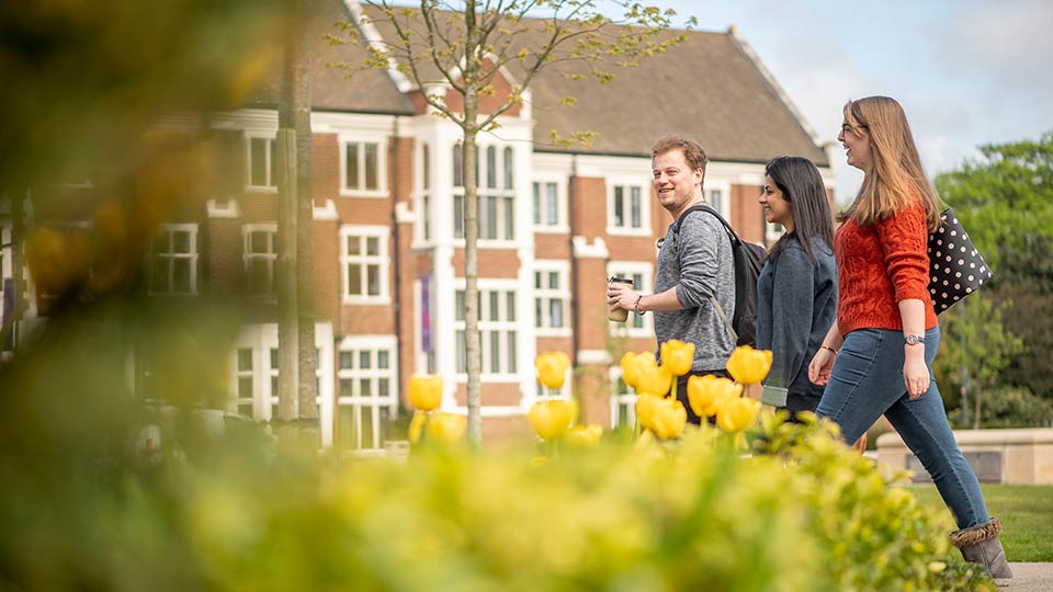 Students walking in front of Hazlerigg building on the Loughbrough University campus